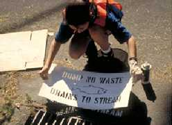 A person uses a large stencil to spray paint Dump No Waste, Drains to Stream
